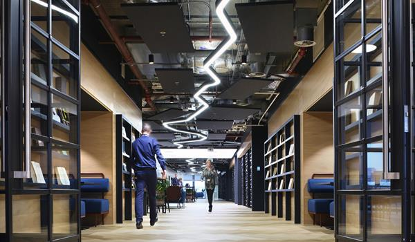 hallway in a modern office with blue bench seating, built in black shelving lining the light coloured wood walls, and a zig zag custom light fixture that runs the length of the hallway